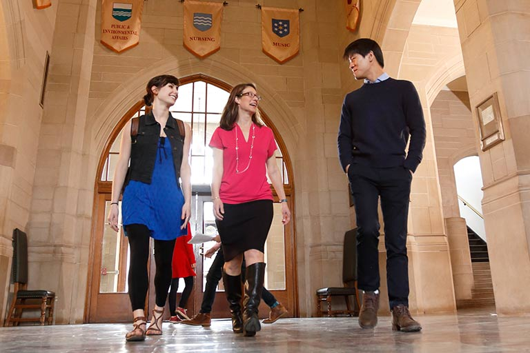 Three people converse as they walk through the halls of the Indiana Memorial Union.