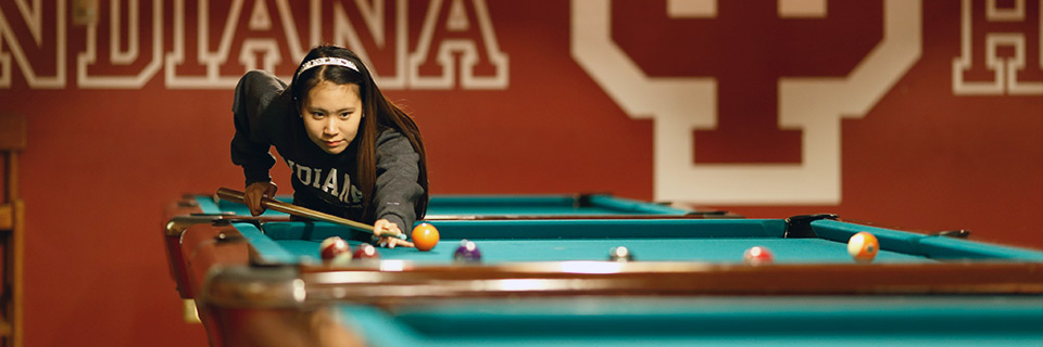 A student plays pool at Bowling and Billiards in the Indiana Memorial Union.