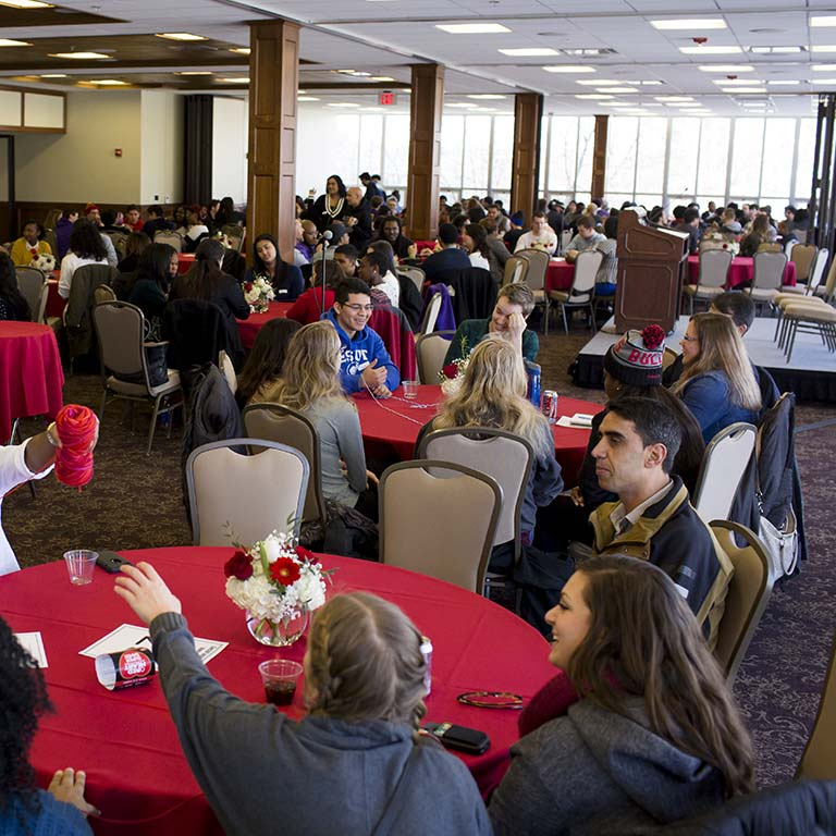 Students sit at tables at an event in the Solarium in the Indiana Memorial Union.