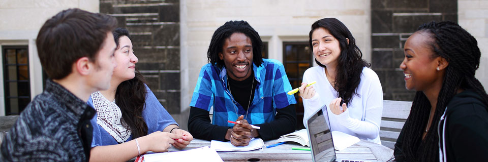 Students study at a table outside.