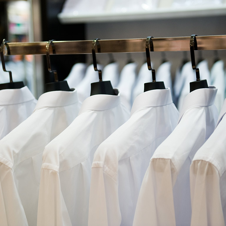 Shirts hang on a rack.