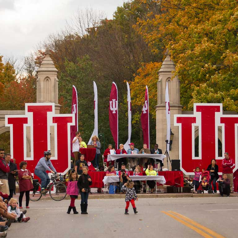 People watch the Indiana University Homecoming parade from the Sample Gates on the IU Bloomington campus.